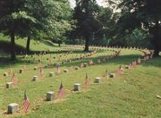 Relatives and others traditionally place flags near veterans' headstones on Memorial Day